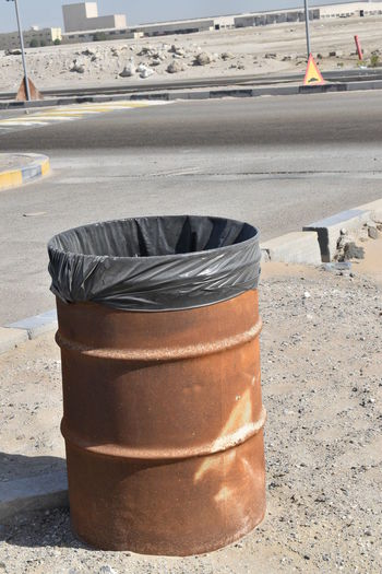 Close-up of garbage bin by street in city