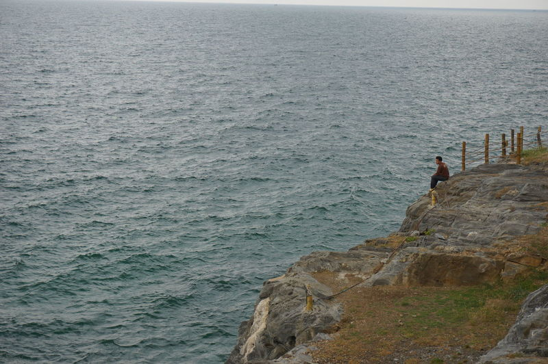 Man sitting on cliff by sea