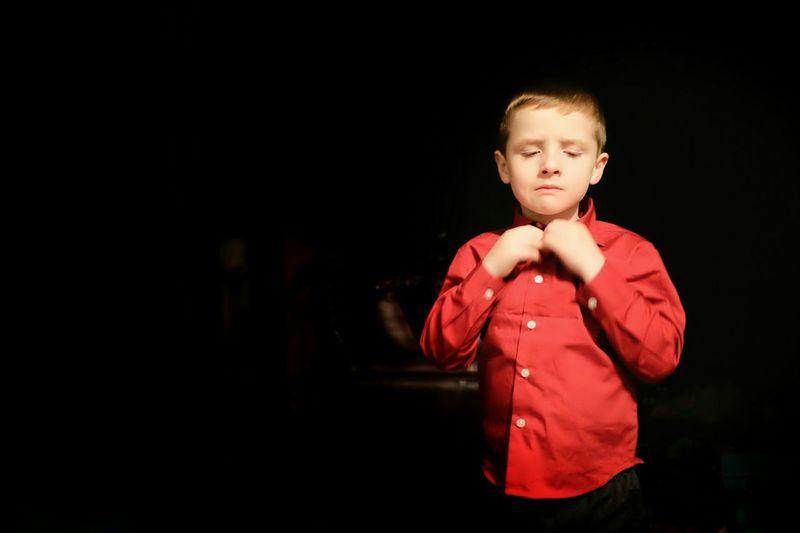 Cute boy in red shirt standing in darkroom