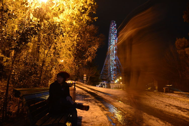 Woman Sitting On Bench By Ghost In Amusement Park At Night During Winter