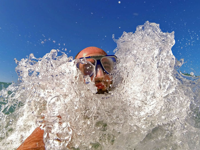 Man Wearing Swimming Goggles In Sea Against Clear Blue Sky