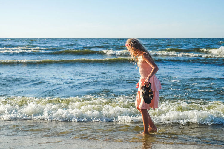 Side View Of Girl Standing On Shore At Beach Against Sky