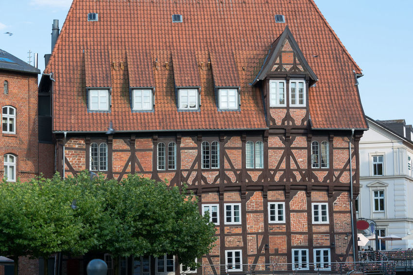 Half-timbered red brick houses near the river on the old harbor Lueneburg, Germany Building Exterior Architecture Built Structure Building Window Residential District House Day No People Sky Nature Roof Outdoors City Tree Plant Low Angle View Brick Row House In A Row Apartment