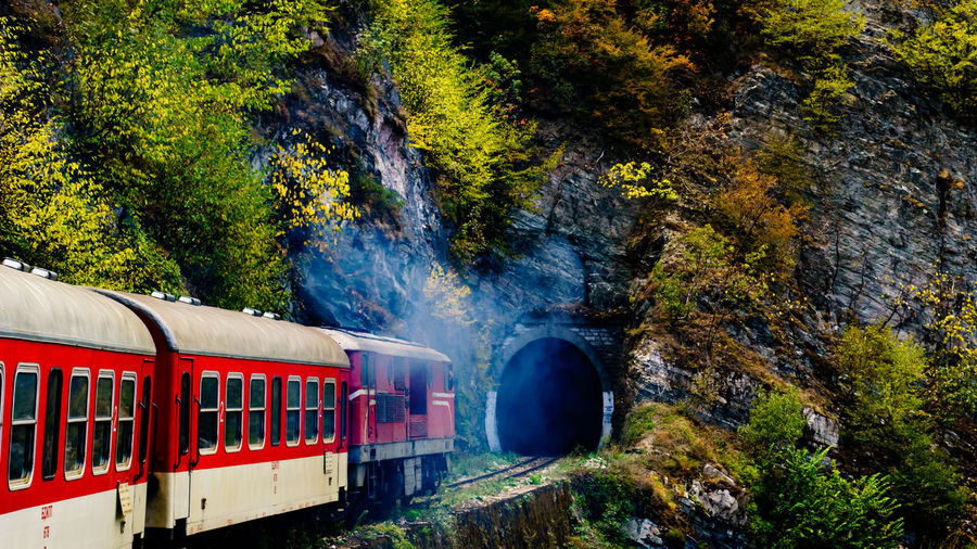 Wide View Of Train Entering Tunnel In Mountainous Landscape