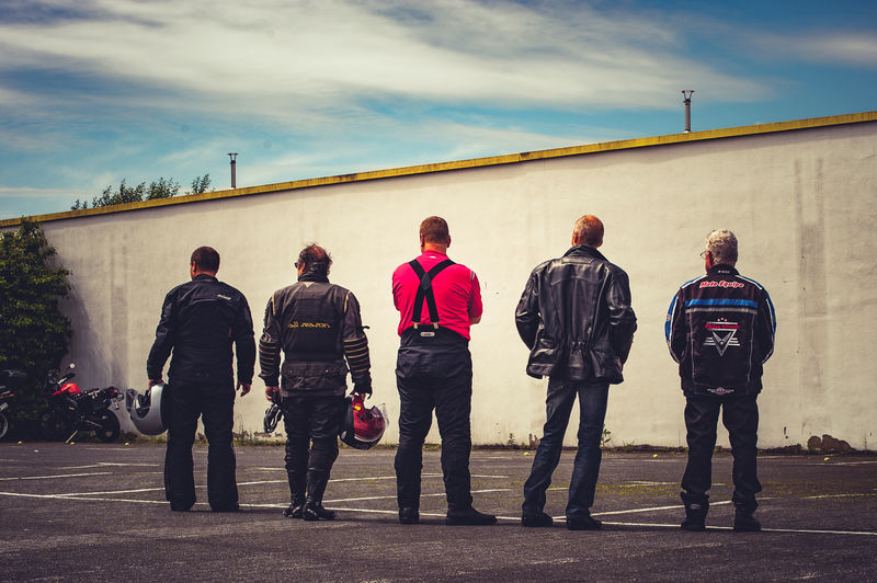 Rear view of bikers standing by wall against sky