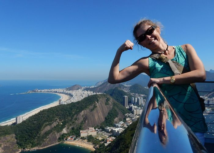 Smiling young woman showing bicep at observation point