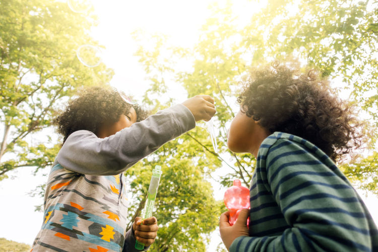 Low Angle View Of Brothers Blowing Bubbles While Standing Against Trees At Park