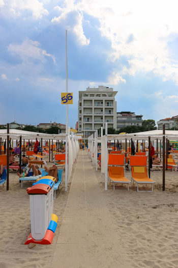 Walkway amidst deck chairs at beach against sky