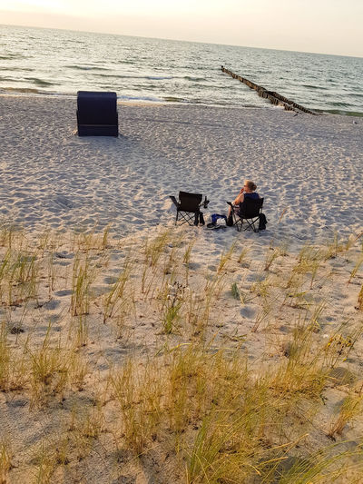 Rear view of a woman on the beach in a deck chair Water Sea Land Beach Sitting Two People Real People Men Nature Lifestyles People Horizon Over Water Beauty In Nature Leisure Activity Seat Sand Day Scenics - Nature Togetherness Outdoors #NotYourCliche Love Letter