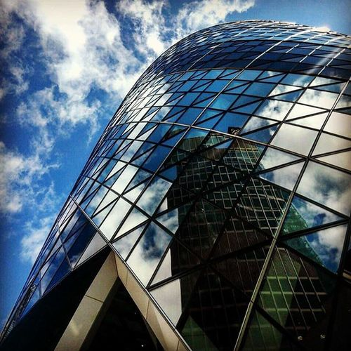 Okurka Gherkin London England business center sky clouds building