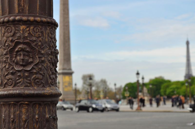 Close-up of carving on metallic pole with luxor obelisk and eiffel tower against sky