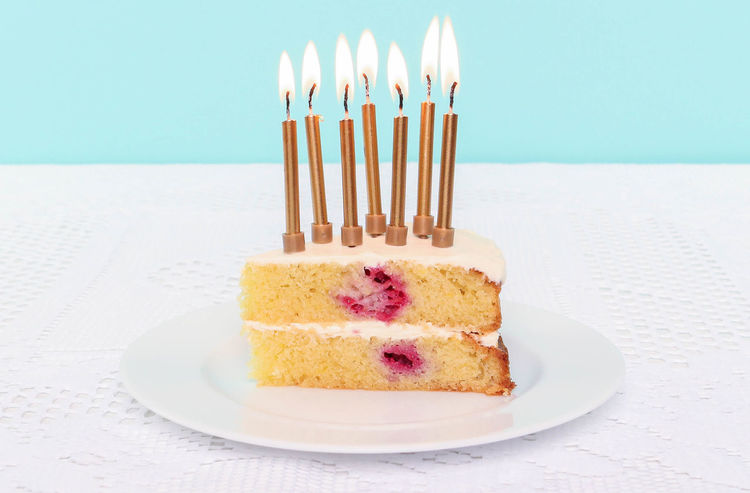 Slice of birthday cake with seven candles. Seven Birthday Birthday Cake Birthday Candles Blue Background Burning Cake Cake Slice Candle Celebration Close-up Day Dessert Flame Food Food And Drink Freshness Indoors  Indulgence No People Plate Raspberry Pink Table Temptation Yellow Cake