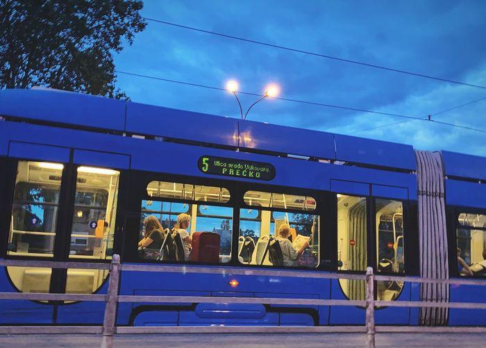 A tram Transportation Public Transportation Text Mode Of Transportation Rail Transportation Illuminated Architecture Sky Dusk Train Blue Cloud - Sky Train - Vehicle Travel Western Script Communication Nature