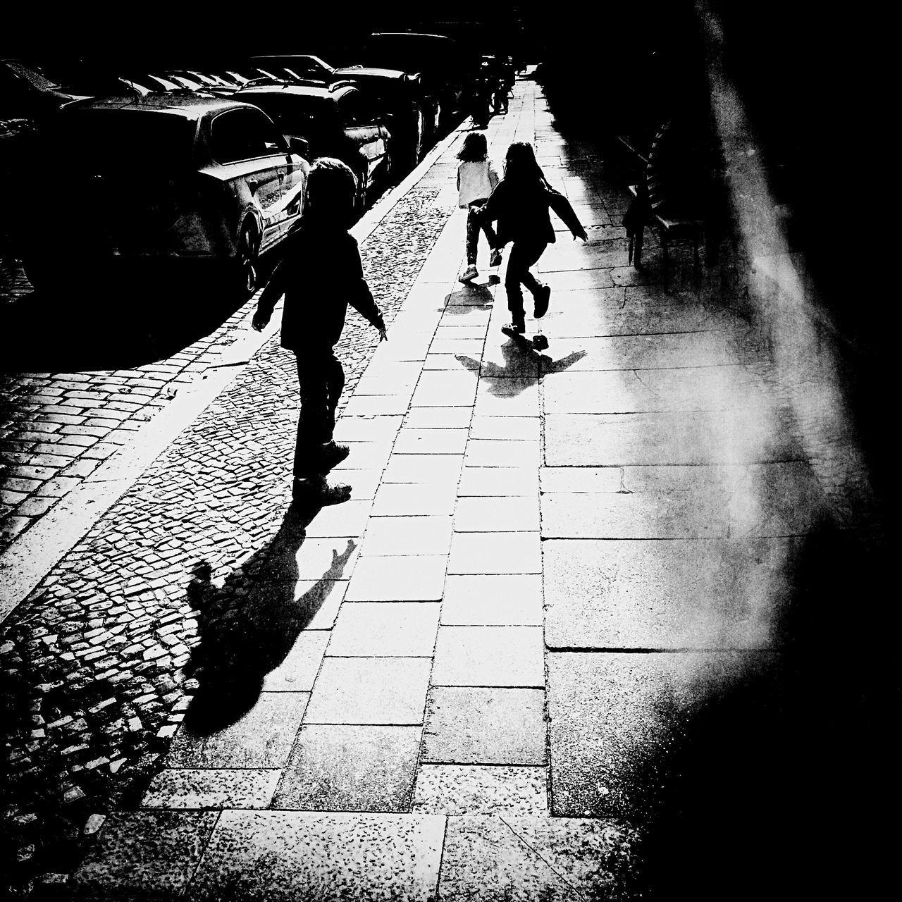 Children Running On Sidewalk By City Street