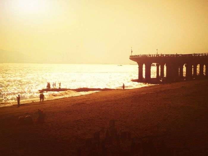 Water Sea Sunset Beach Sand Bridge - Man Made Structure Built Structure Shore Outdoors Scenics Orange Color EyeEm Gallery Hello World Taking Photos Hi! EyeEm Best Shots EyeEm Best Edits People And Places Sunset_collection Sunset Silhouettes Sunset Collection Check This Out