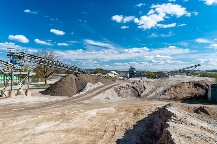 Heaps of gravel and crushed on blue sky at an industrial cement plant.