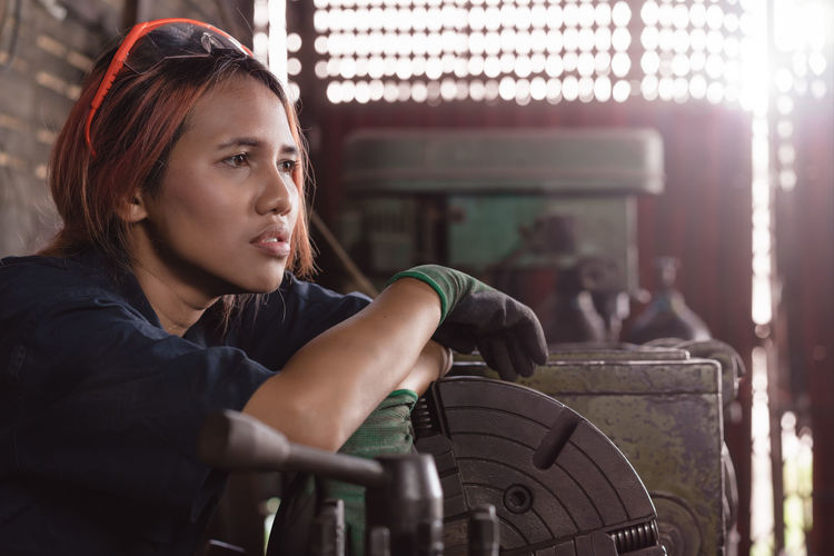 Thoughtful female mechanic at garage
