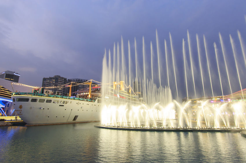"Shenzhen, China - August 22,2015: Dancing Fountains in New Sea World Plaza, one of the landmark of Shenzhen, at sunset with the Minghua ship on its center. The ship was originally known as Anceevilla and was later renamed ""Minghua"" by the chinese who bought it. Anceevilla Architecture ASIA Built Structure China City Cityscape Cloud Cloud - Sky Dancing Fountain Guandong City Illuminated Modern Nature Night No People Outdoors Reflection Shenzhen Shenzhen.China Sky Stock Market Travel Destinations Water Waterfront"
