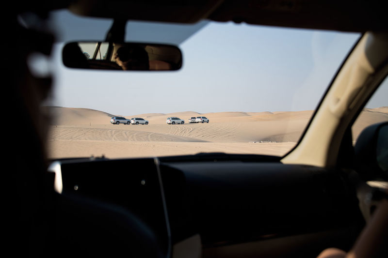 Off-Road Vehicles Seen Through Car Windshield At Desert