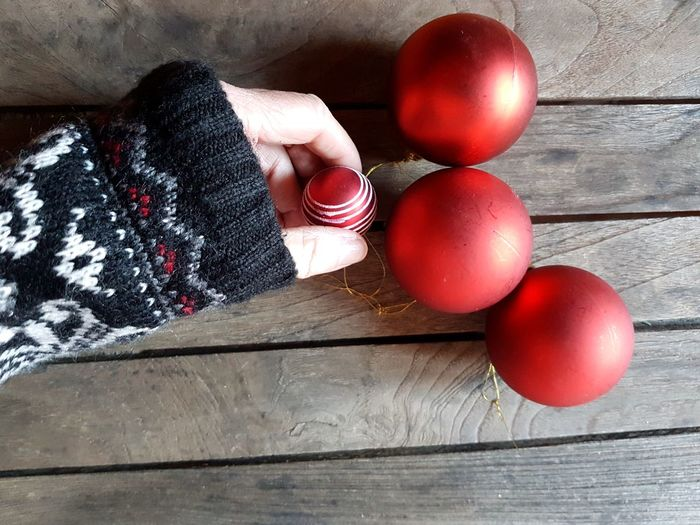 Cropped Hand Holding Bauble On Wooden Table