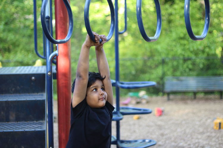 Boy Hanging On Monkey Bars At Playground