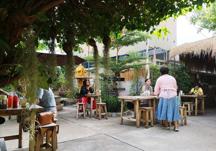 People sitting on table by chairs against trees