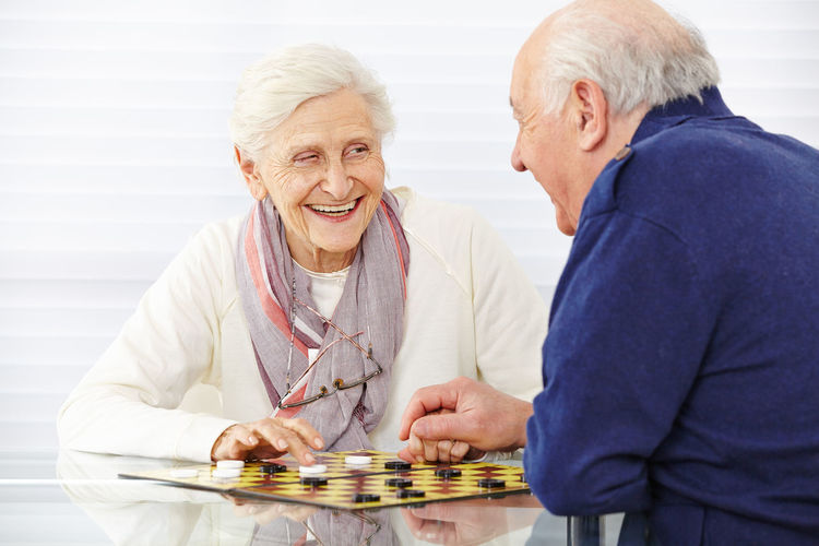 Smiling senior people playing chess at home