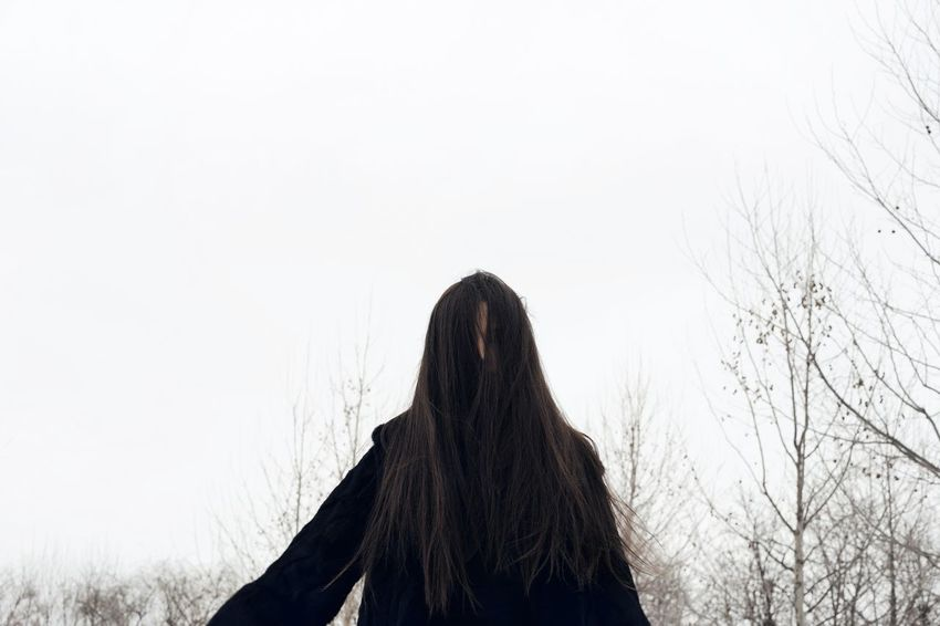 Cold Temperature Long Hair Winter Face Hidden Hiding Face Fur Coat One Woman Only Minimalism Minimal Trees Bare Trees Warm Clothing Women Silhouette Bare Tree Branch Tree Trunk Tranquil Scene Cold