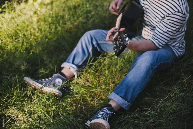 Low section of man playing guitar on grass