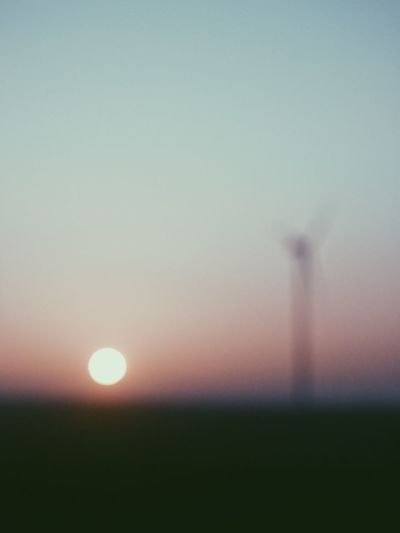 Defocused image of silhouette field against clear sky during sunset