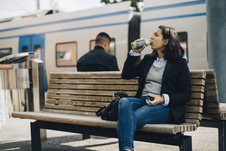 Full length of woman sitting on bench