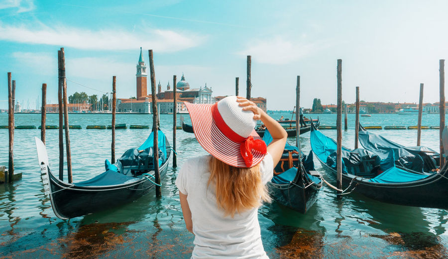 Rear view of woman standing by grand canal against sky