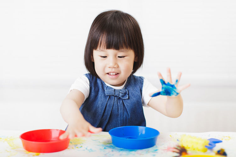 Happy girl playing with paints on table