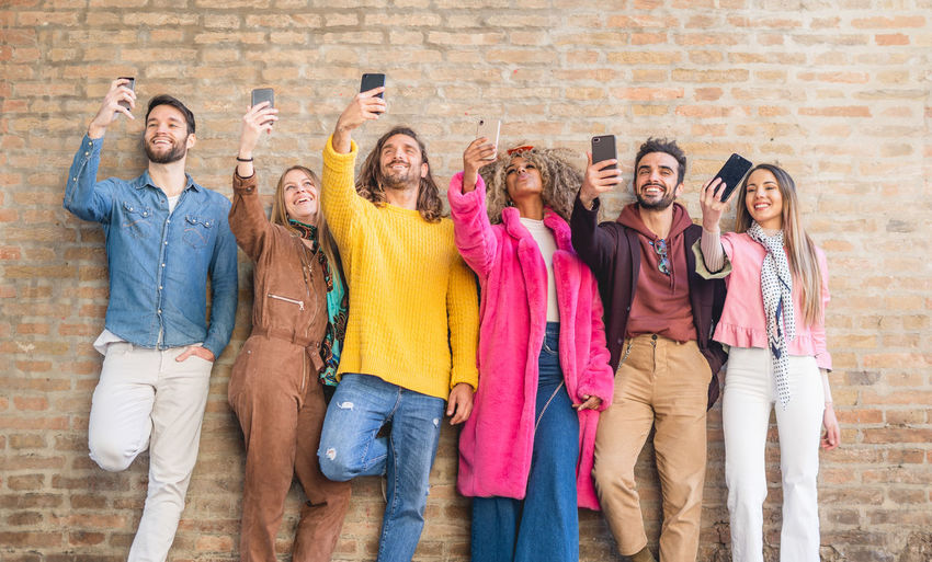 Group of people taking a selfie outdoors against a brick wall Happiness Smiling Young Adult Friendship Togetherness Emotion Cheerful Group Of People Young Men Portrait Young Women Men Women Enjoyment Brick Positive Emotion Human Limb Human Arm Excitement Fun Standing Adult Technology Smart Phone Selfie Taking Photos Taking Selfies Outdoors Standing Wall - Building Feature Branch Wall Against