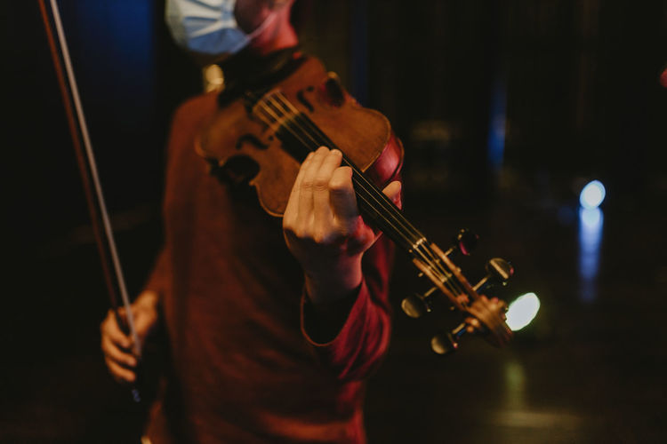 Midsection of man playing violin at music concert