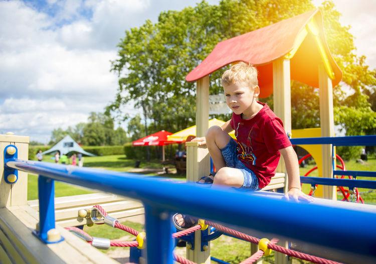 Boy sitting on jungle gym at playground