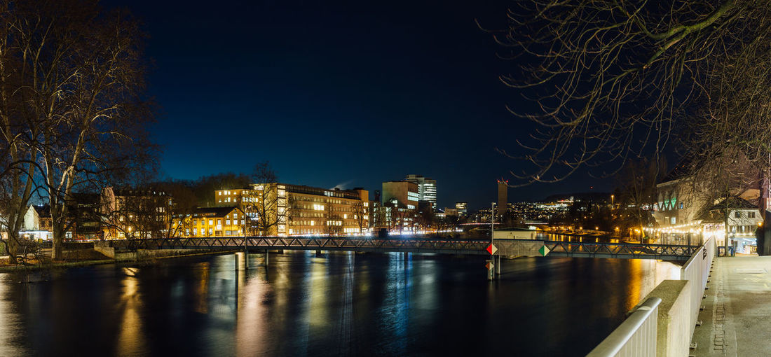 Wide angle long exposure of the limmat river in zurich city center at night.
