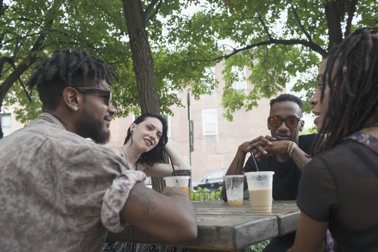 A group of friends having a conversation at a picnic table.