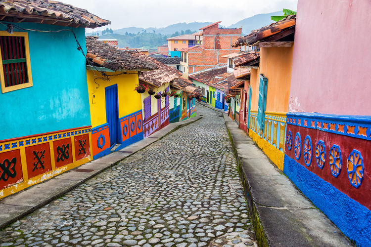 Colorful colonial houses on a cobblestone street in Guatape, Antioquia in Colombia Antioquia Architecture Art Bright Building Cobblestone Colombia Color Colorful Colors Countryside Destination Guatape Holiday Houses Medellín Multi Colored Municipality South America Street Tourism Tourist Town Travel View