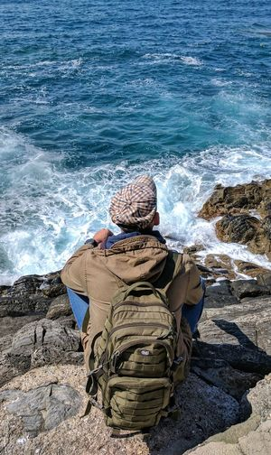 Sea Beach Water Sand Shore Wave One Person Nature Real People Leisure Activity Day Rear View Outdoors Lifestyles Vacations Beauty In Nature Horizon Over Water Men Adult Backpack Hat Young Adult From Back Chilling Rest