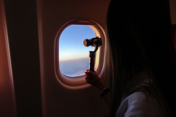 Woman filming view with camera while sitting in airplane