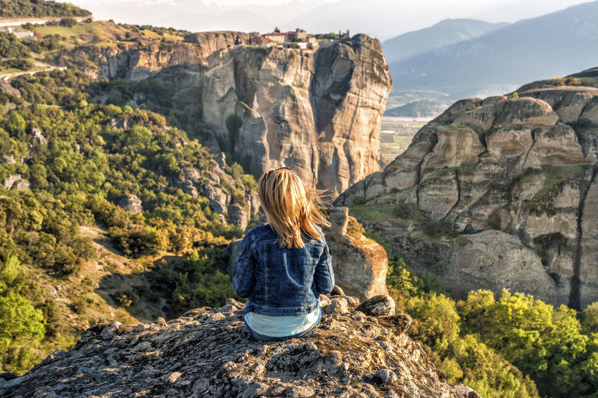 On top of the world Meteora Adult Adventure Beauty In Nature Blond Hair Casual Clothing Cliff Landscape Leisure Activity Mountain Mountain Range Nature One Person Physical Geography Real People Rear View Rock - Object Scenics Sky Women Young Women