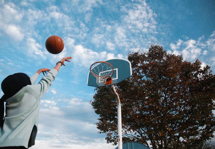 Woman Throwing Ball In Basketball Hoop Against Sky