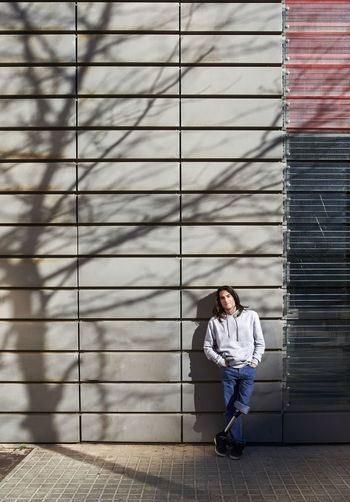Full length of young man looking away against wall