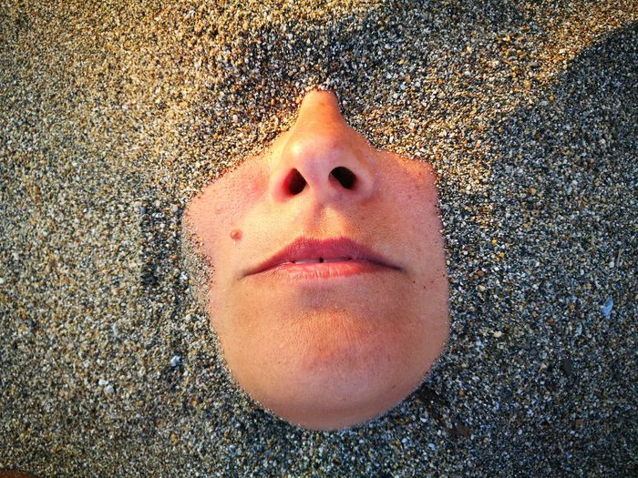 Woman face buried in sand at beach