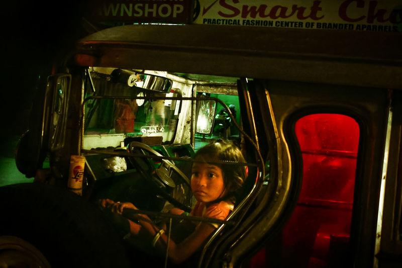 Portrait of woman seen through car windshield