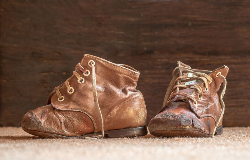 a few ancient children's shoes Shoe Pair Leather Brown Still Life Close-up Shoelace Two Objects No People Boot Indoors  Flooring Absence Personal Accessory Compatibility Fashion Focus On Foreground Selective Focus Table Nature Menswear Lace - Fastener Children's Shoes Antique Ancient