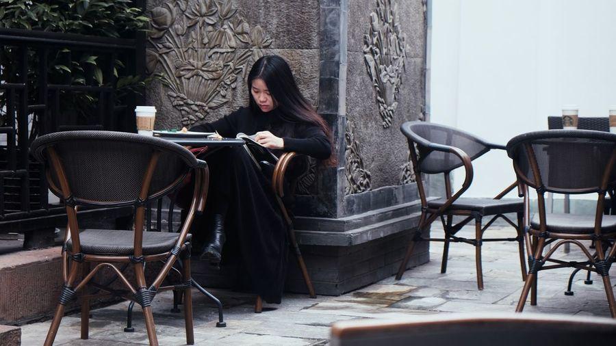 Woman reading menu while sitting at cafe