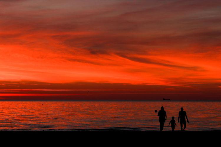 Silhouette people looking at sea against orange sky