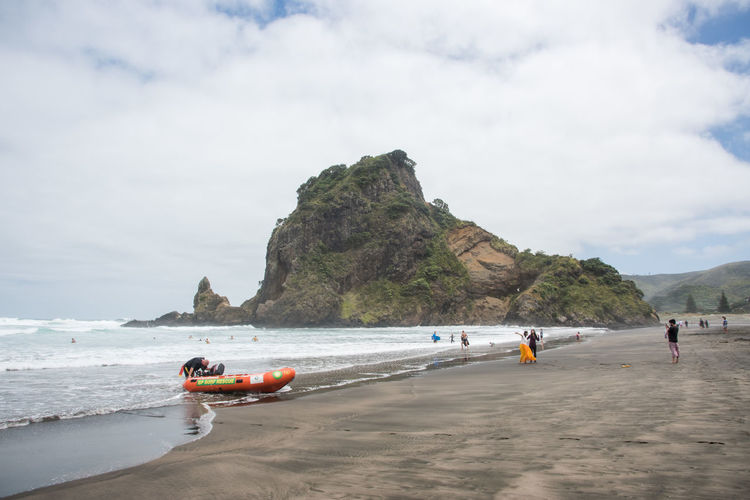 Auckland, New Zealand-December 17,2016: Stunning black sand Piha Beach with lifeguard inflatable and tourists on an overcast day in Auckland, New Zealand Auckland Lion Rock Swimming Tasman Sea Travel Wave Beach Black Sand Geology Group Of People Inflatable  Leisure Activity Lifeguard  Lifestyles Mountain Nature Nautical Vessel New Zealand Piha Power In Nature Real People Sea Volcanic Landscape Volcano Water